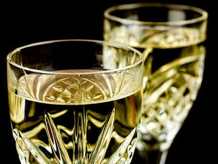 sucessful: Chilled White Wine in a Cut Crystal Glass Against a Black Backgorund Stock Photo
