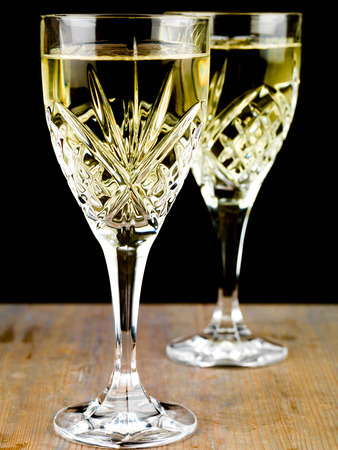 Chilled White Wine in a Cut Crystal Glass Against a Black Backgorund Stock Photo
