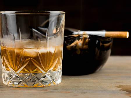 Glass of Scotch Whiskey on the Rocks and a Cigarette Burning in an Ashtray Stock Photo