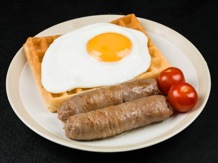 Breakfast Food of Fried Egg and Sausages on Waffles