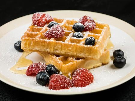 신선한 라즈베리와 블루 베리와 여드름이나 시럽과 설탕을 섞은 와플의 건강한 아침 식사