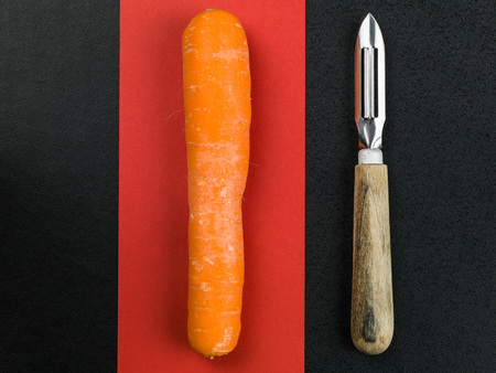 handled: Raw Carrot With a Wooden Handled Vegetable Peeler