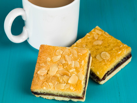tarde de cafe: Cherry Bakewell Tarts With a Cup or Mug of Tea or Coffee Against a Blue Background Foto de archivo