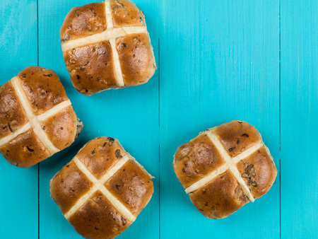 Four Hot Cross Buns Easter Food Against a Blue Background