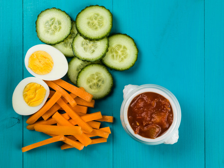 Egg Carrot and Cucumber Crudites With Tomato Salsa Against a Blue Background