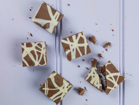 Individual Decorated and Iced Chocolate Tiffin Cakes Against a Lilac or Purple Background