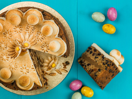 Easter Simnel Cake With Marzipan Icing and Decorations Against a Blue Background