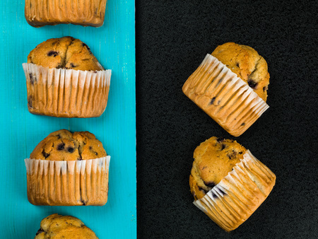 Selection of Fresh Blueberry Muffins Against a Blue and Black Background Stock Photo