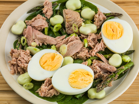 Tuna Fish Salad with Broad Beans Boiled Eggs and Asparagus On a Wooden Chopping Board