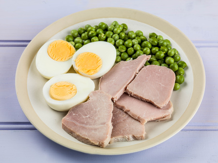 lillac: Cooked Ham and Egg Salad With Green Garden Peas Against a Wooden Lillac Table Top Stock Photo