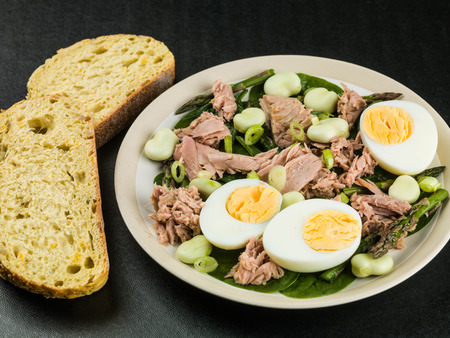 Tuna Fish Salad with Broad Beans Boiled Eggs and Asparagus Against a Black Background Stok Fotoğraf