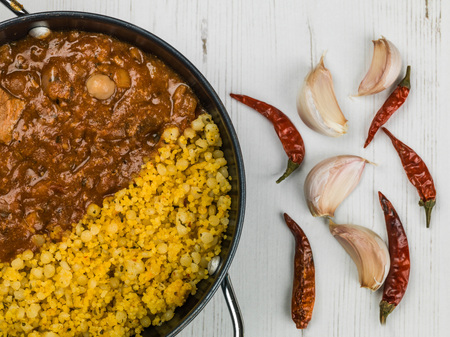 Lamb Tagine With Couscous and Chickpeas Against a White Background Stock Photo