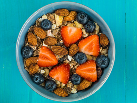 Breakfast Muesli Cereals With Strawberries and Blueberries Fruit Against a Blue Background