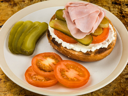 Ham Tomato and Cheese Spread Sesame Bagel With Gherkins Sitting on an Oven Tray