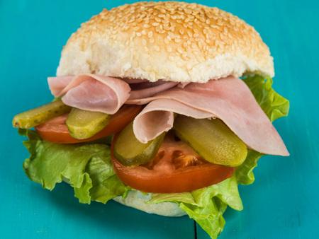 Ham Salad Sesame Seed Bread Roll or Bun Sandwich Against a Blue Background Stock Photo