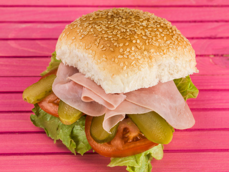 Ham Salad Sesame Seed Bread Roll or Bun Sandwich Against a Pink Background Stock Photo