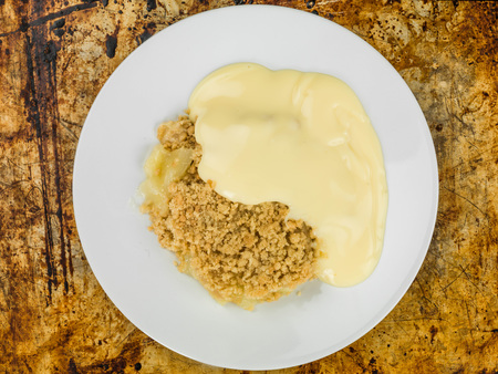 Apple Crumble Dessert Served With Hot Custard On A Distressed Oven Tray