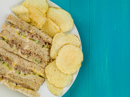 Tuna Sweetcorn and Cucumber Oatmeal Bread Sandwich With Potato Crisps Against a Blue Wooden Background
