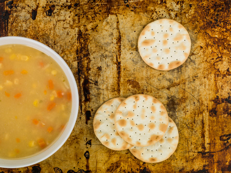 Chicken Sweetcorn and Noodle Soup With Crackers Against a Distressed Oven Tray Stock Photo