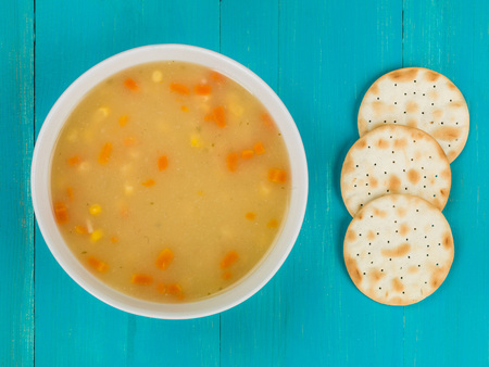 Chicken Sweetcorn and Noodle Soup With Crackers Against a Blue Wooden Background Stock Photo
