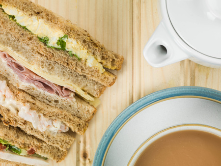 malted: Selection of Assorted Sandwiches in Brown Bread With a Cup of Tea or Coffee Against a light Pine Wood Background