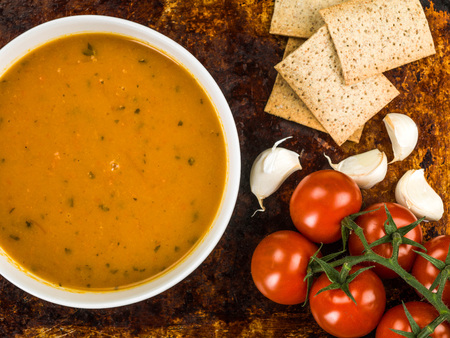 galletas integrales: Bowl of Carrot and Coriander Soup Against a Distressed Burnt Oven or Baking Tray