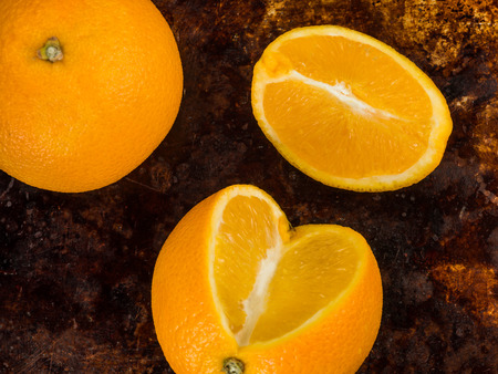 Fresh Ripe Juicy Oranges And Orange Segments Against a Distressed Oven or Baking Tray Reklamní fotografie