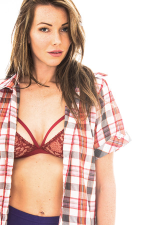 Carefree Relaxed Young Woman Wearing and Open Mans Shirt and a Red Bra Against a White Background