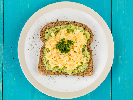 Scrambles Eggs and Avocado on Toasted Wholemeal Brown Bread Against a Blue Wooden Background 版權商用圖片