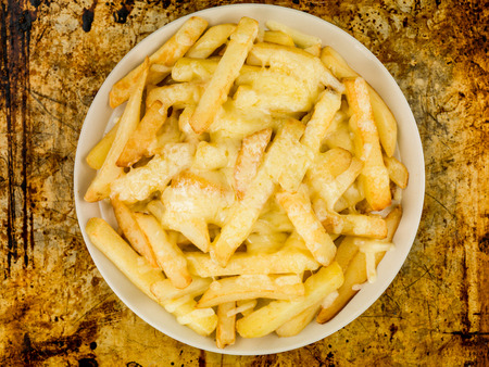 Bowl of Fried and Grilled Cheesy Chips Against a Distressed Oven or Baking Tray Background