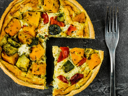 chunky: Freshly Baked Vegetable Quiche or Flan Against a Black Slate Tile Stock Photo