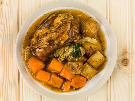 chunky: Chicken Stew With Vegetables and Gravy Against a Light Pine Wood Background
