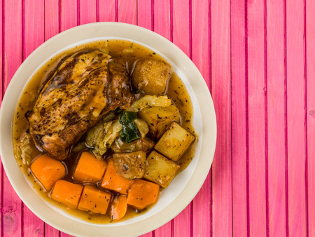 Chicken Stew With Vegetables and Gravy Against a Pink Wooden Background Stock Photo