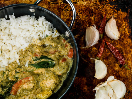Thai Green Chicken Curry With Rice Against a Distressed Used Oven or Baking Tray