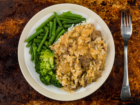 Beef Stroganoff With Long Grain Rice Green Beans and Broccoli Against A distressed Oven of Baking Tray