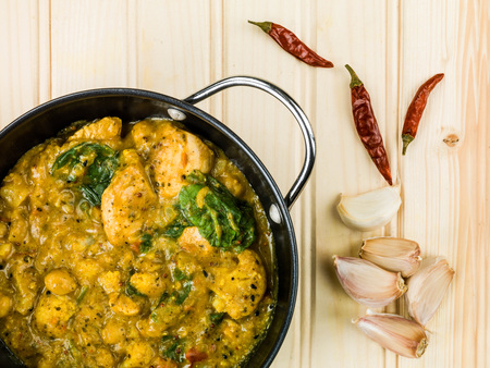 garbanzos: Keralan Chicken Curry In Coconut Sauce and Vegetables Against a Light Pine Wood Background