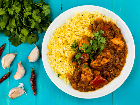 Chicken Jalfrezi Curry With Basmati Spiced Rice Against a Blue Wooden Background