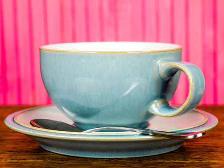 China Cup and Saucer With a Tea Spoon Against A Pink Background Stock Photo