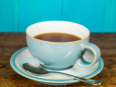 Cup of Black Refreshing Tea In A Cup Against A Blue Background