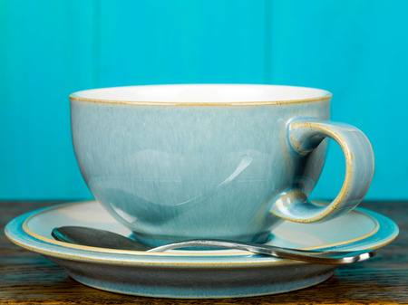 China Cup and Saucer With a Tea Spoon Against A Blue Background