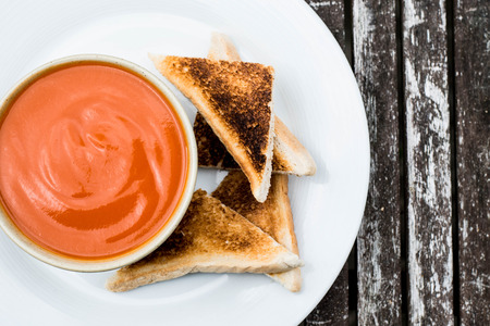 Bowl of Tomato Soup With Toast on A Rustic Wooden Table Top Background