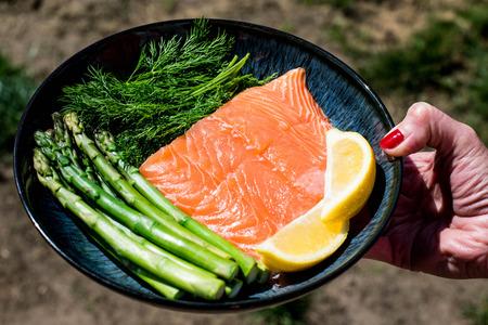 Держите пластину свежего сырого здорового филе лосося со спаржей и лимоном Фото со стока