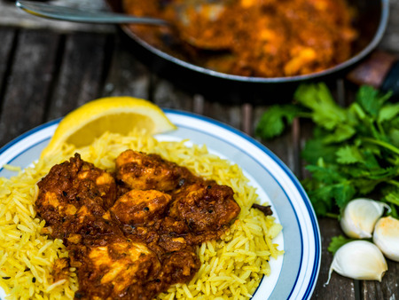 Chicken Balti Indian Curry Takeaway Meal Wth Pillau Rice Against a Dark Wooden Background