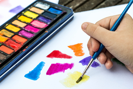 Child Painting With Watercolor Paints on a White Paper Book In Natural Light Stock Photo