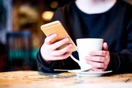 Holding and Texting On A Mobile or Cell Phone In A Cafe or Bar