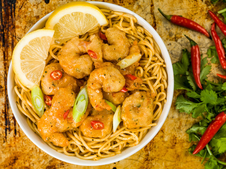 Crispy Deep Fried Prawns With Sweet Chilli Sauce and Noodles Against A Distressed Baking or Oven Tray Stock Photo