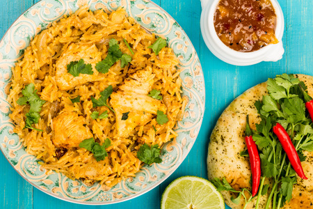 Курица индийского стиля Biryani Curry с рисом и Naan Хлеб с кориандром и красными чили на синем деревянном фоне Фото со стока