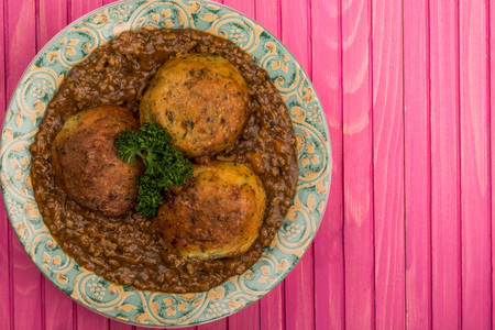 Minced Beef and Onions With Dumplings or Cobblers Meal On A Pink Wooden Background