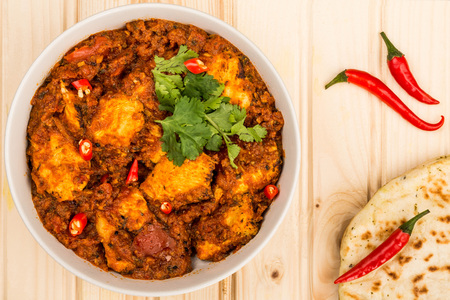 Indian Style Chicken Balti Curry With Naan Bread and Red Chillies On A Light Pinewood Background Stock Photo