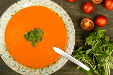 Bowl of Fresh Warming Tomato and Basil Soup On A Green Wooden Background